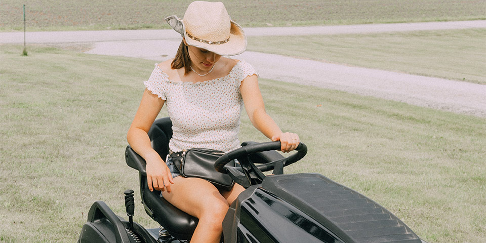 Attractive woman on a lawn mower, wearing a hat of some sorts.